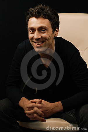 Man leans forward smiling