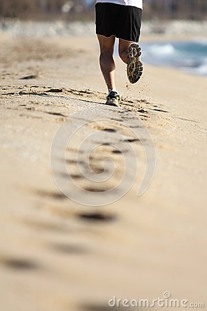 Man legs running on the sand of a beach