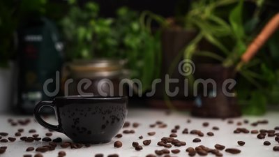 Man legt eine schwarze Tasse heißen Kaffee oder Espresso auf den weißen Tisch mit Kaffeebohnen drauf. stock video footage