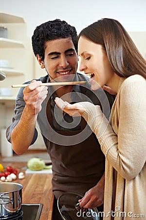 Man letting woman taste soup