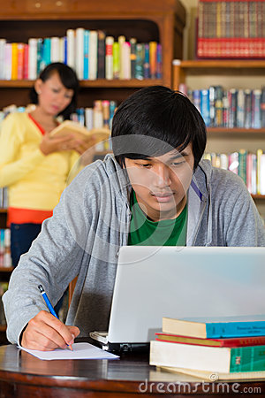 Man in library with laptop