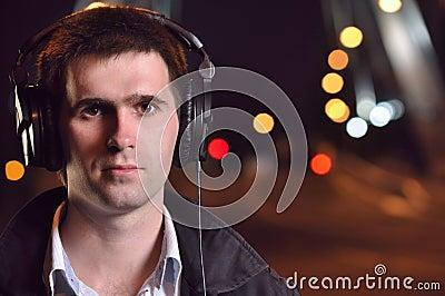 Man listening music at night street