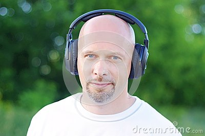 Man listening music outdoors in wireless headset