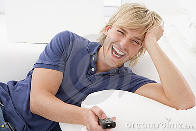 Man in living room holding remote control