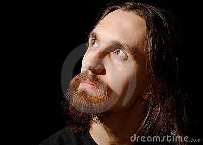 Man with long hair and beard looking up and left