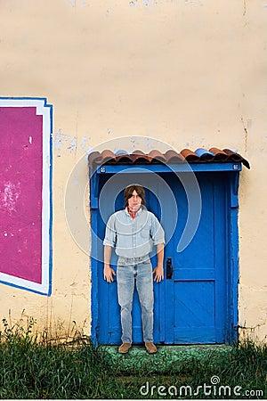 Man With Long Hair Standing Adobe Building Doorway