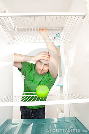 Man looking at apple in fridge