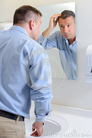 Free Man Looking At Hair In Mirror Royalty Free Stock Images - 89109199