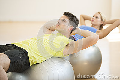 Man Looking Away While Exercising On Fitness Ball At Gym
