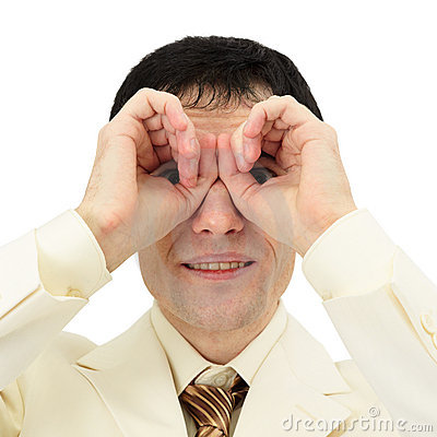 Man looking through fingers like binoculars