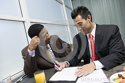 Man Looking At His Business Partner Signing Document