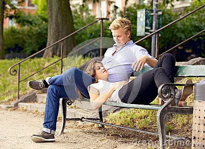 Man Looking at His Girlfriend Resting on His Lap