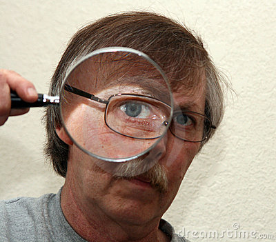 Man looking through magnifier