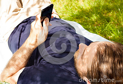 Man looking at mobile phone while laying on grass