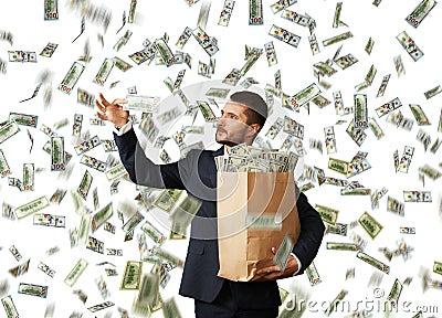 Man looking at money under dollar s rain