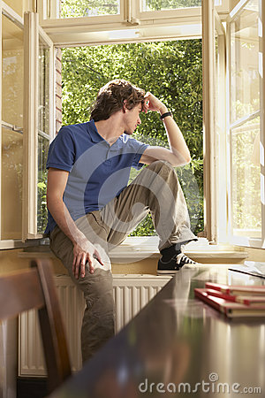 Man Looking Out Of Window Sill In Study Room