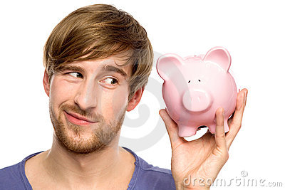 Man looking at piggy bank suspiciously