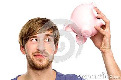 Man looking at piggy bank suspiciously