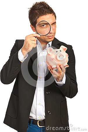 Man looking throught loupe to piggy bank