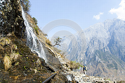 Man Looking Up at Mountainside Waterfall