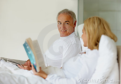 Man looking at wife while she reads a book in bed