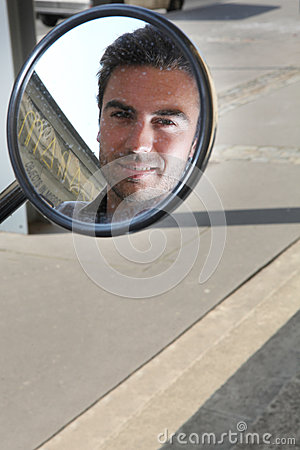 Man looking in the wing mirror