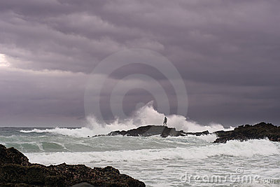 Man looks for shellfish on rocks in stormy sea
