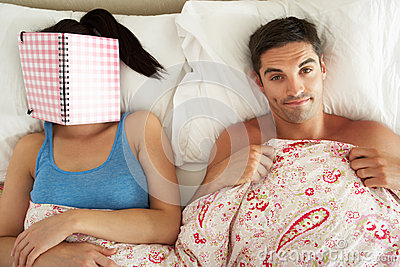 Man Lying In Bed Next To Woman Reading Book