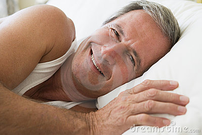 Man lying in bed smiling