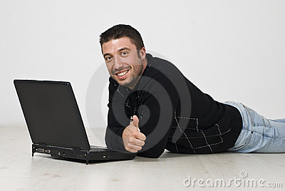 Man lying on floor with laptop and give thumbs