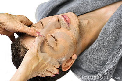 Man lying, gets reiki,acupressure on his face