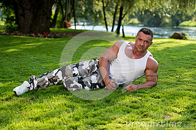 Man Lying On Grass And Holding Bottle Of Water
