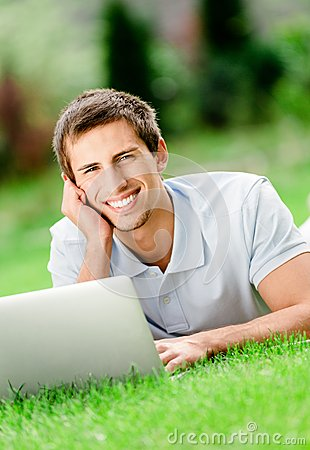 Man lying on the grass works at the laptop