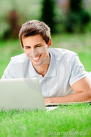 Man lying on the green grass works at the laptop