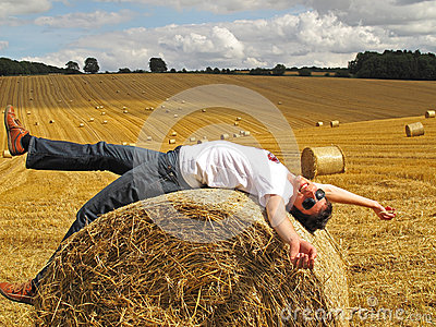 Man lying on hay bale
