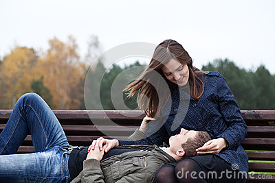Man lying in lap of young woman