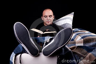 Man lying on the sofa reading a book,