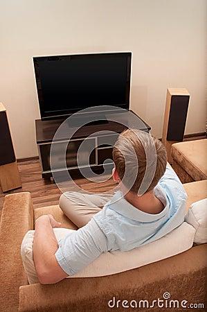 Man lying on sofa watching TV