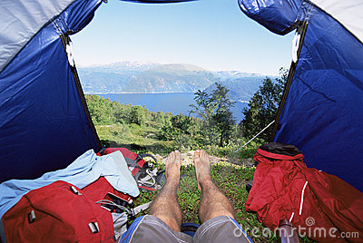 Man lying in tent with a view of lake