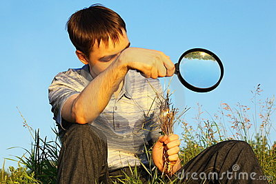 Man with magnifier is sitting and burning grasses