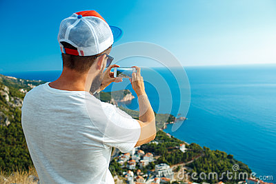 Man makes photos by a smartphone on the background of sea coast, Stock Photo