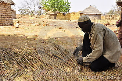 Man making straw wall for african houses, roof Editorial Stock Photo