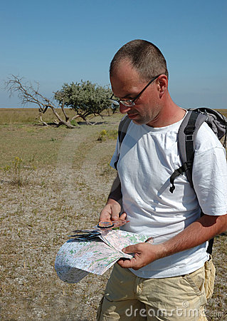 Man with map and compas -  orienteering outdoors