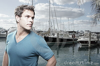 Man at a marina glancing over his shoulder