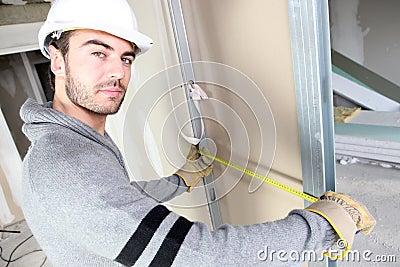 Man measuring width of wall