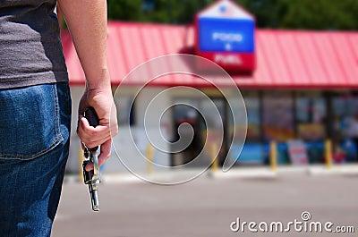 Man med vapnet som är klart att råna en servicebutik