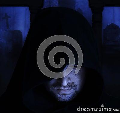 Man in an medieval hood on a churchyard