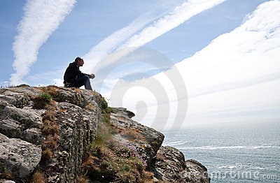 Man meditating on cliff top