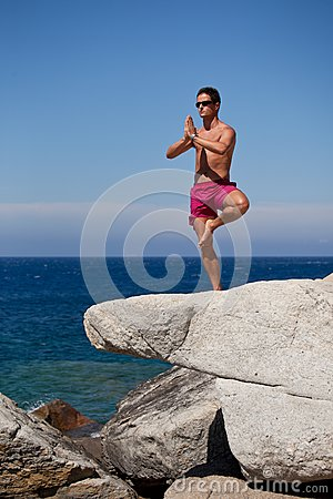 man meditating on a rocky beach