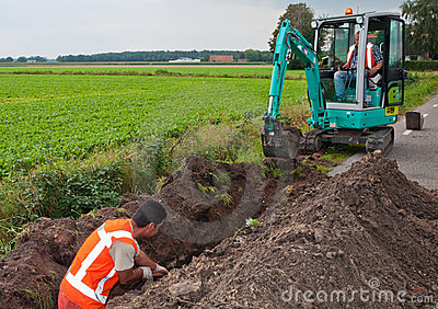 Man and mini excavator dig a trench to lay cables Editorial Stock Photo